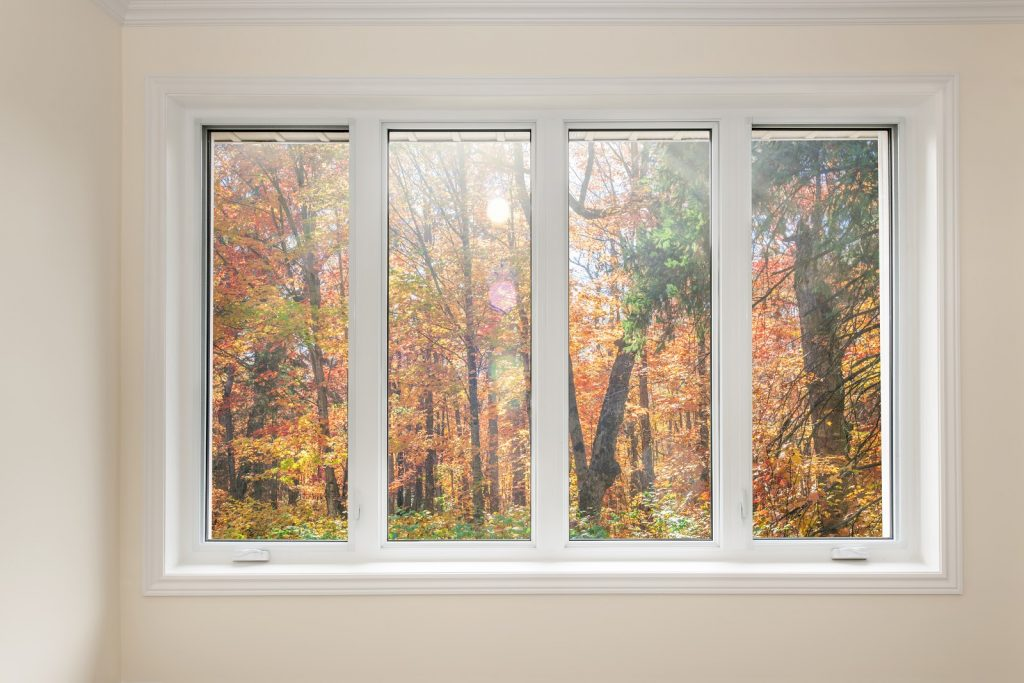 A closed casement window with four sashes overlooking an autumn forest