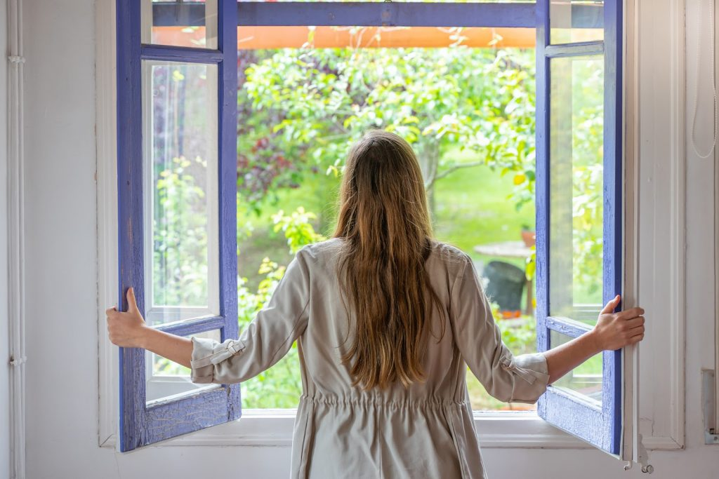 A woman looking outside in-swinging casement windows while holding the two sashes