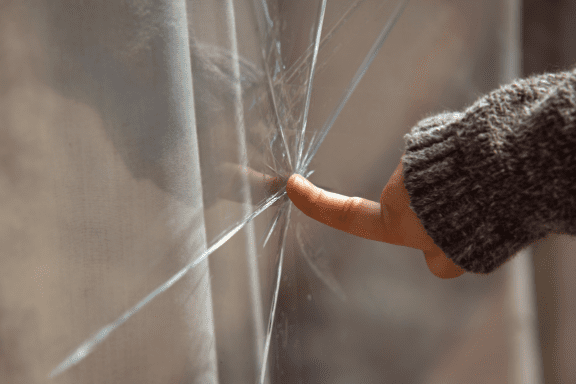 Close up of a child's hand touching cracked window glass