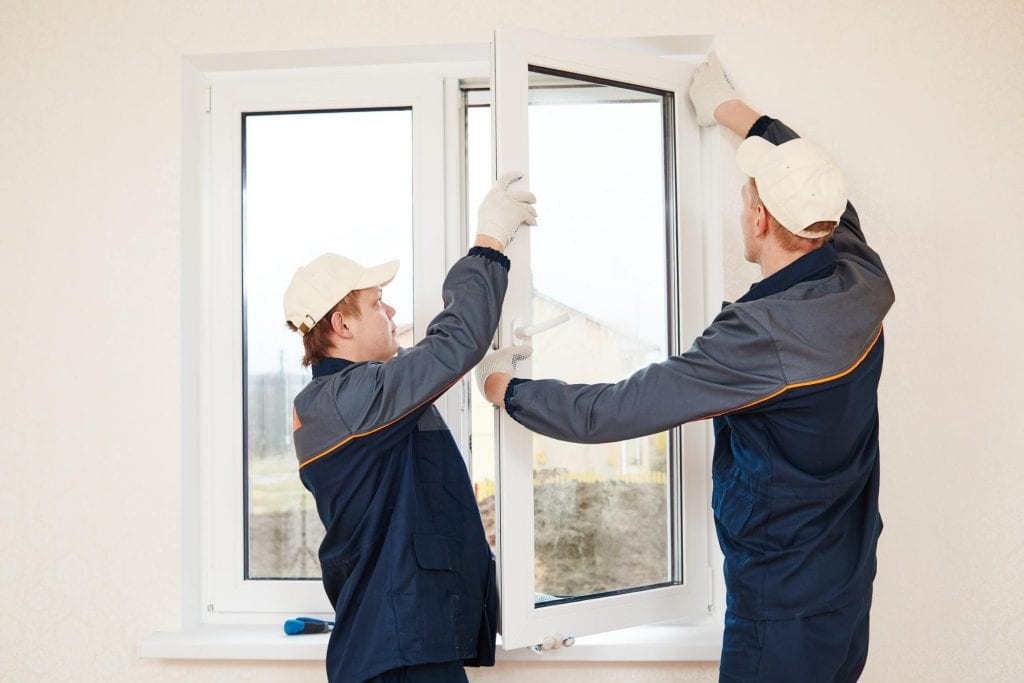 Two people installing an energy-efficient window