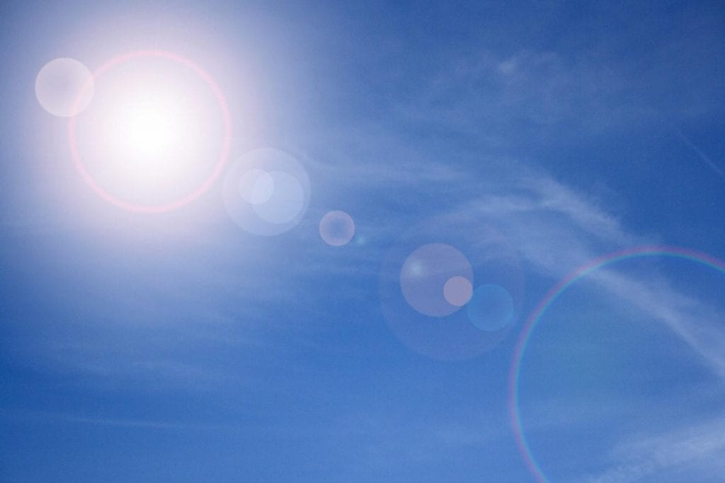 A cloudless blue sky and the sun with light flaring