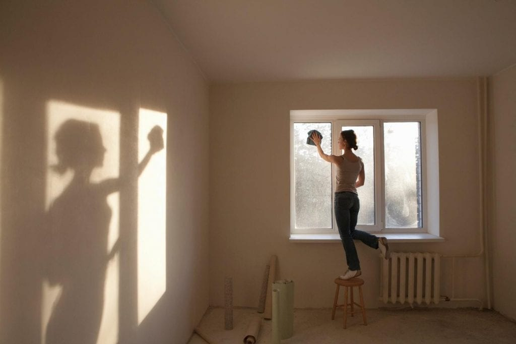 A woman cleaning her home's windows in Barrie