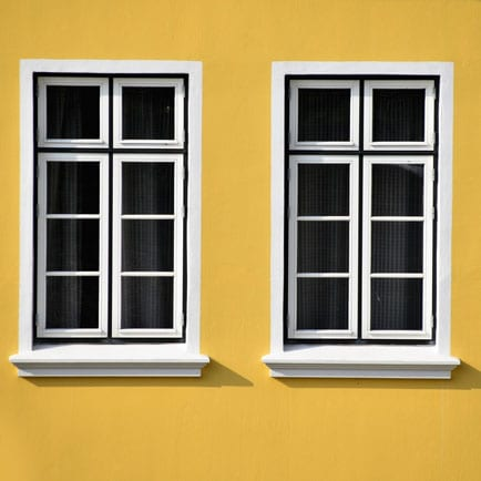 Two white-framed vinyl windows, yellow wall