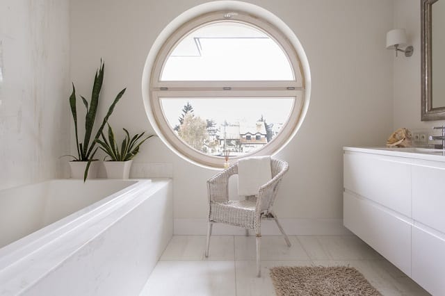 Big, round glass window in a bathroom