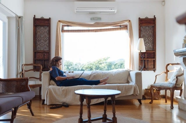 Woman sitting on a couch in a room with huge open windows and surrounded by wooden furniture.