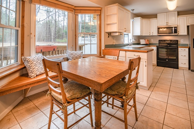 A breakfast nook and kitchen with plenty of natural light from windows