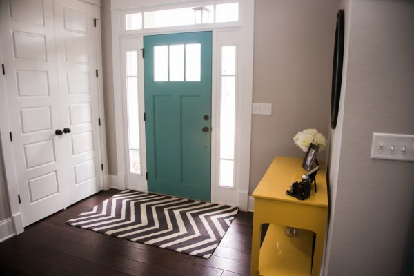 Entryway with a turquoise door and transom windows