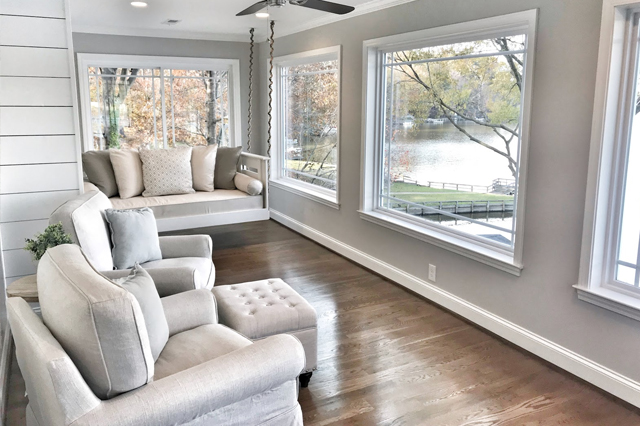 A sunroom with couches, overlooking the lake