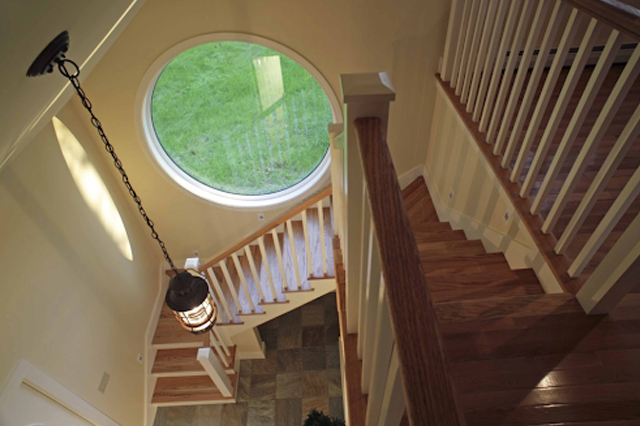 Round fixed window along the side of a sweeping staircase