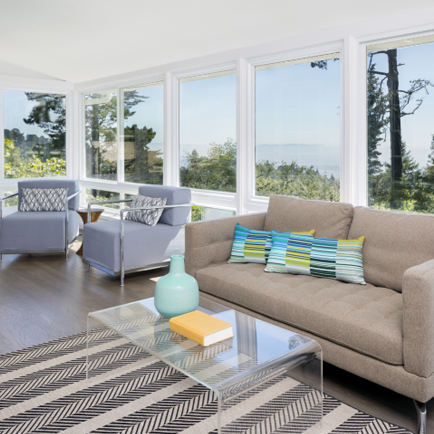 A bright sunroom with couches and a coffee table
