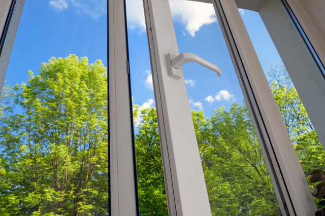 Close up of vinyl windows with Low-E glass looking out into a forest view