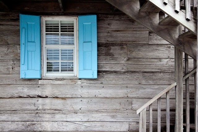 Glass window with blue shutters