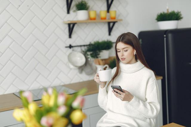 Woman receiving a notification from her smart doorbell on her smartphone