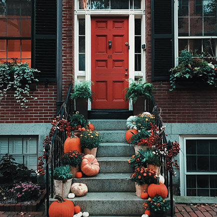 A brick red front door with autumn decorations on its steps.