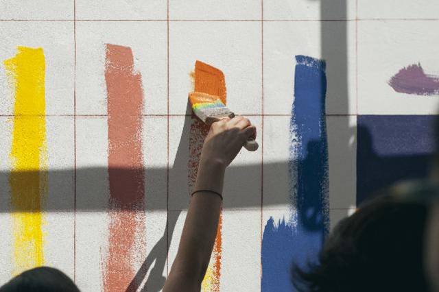Person applying different shades of paint on the wall