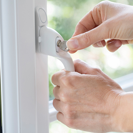 Hands turning a key to open a window lock