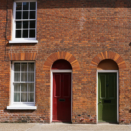 Bricked homes with red and green front doors