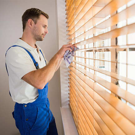 Man using a soft rag to clean window blinds