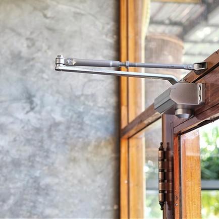 Close up of a door closer installed on a modern glass door