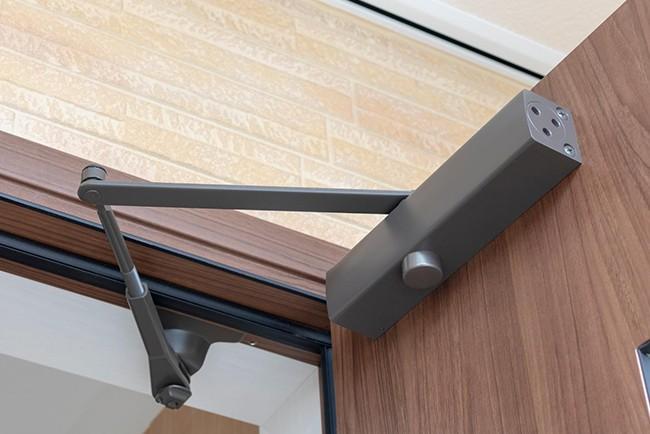 A door closer mounted on a wooden door that is open