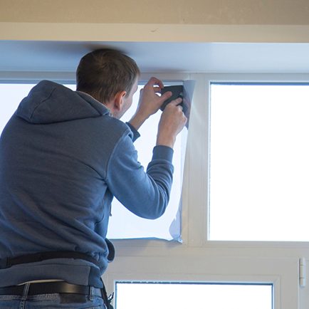 Professional window installer removing window film from glass