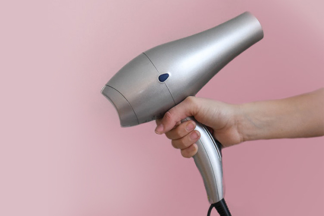 Hands holding hairdryer