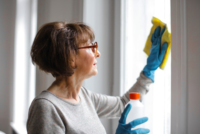 Woman cleaning glass window with rag