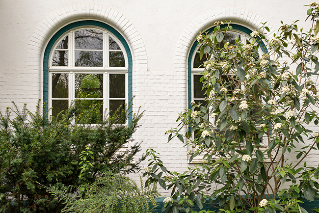 A home with shrubbery surrounding the first-level windows