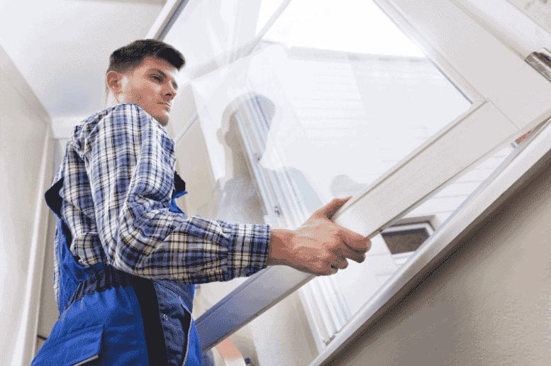 A window contractor examining a window