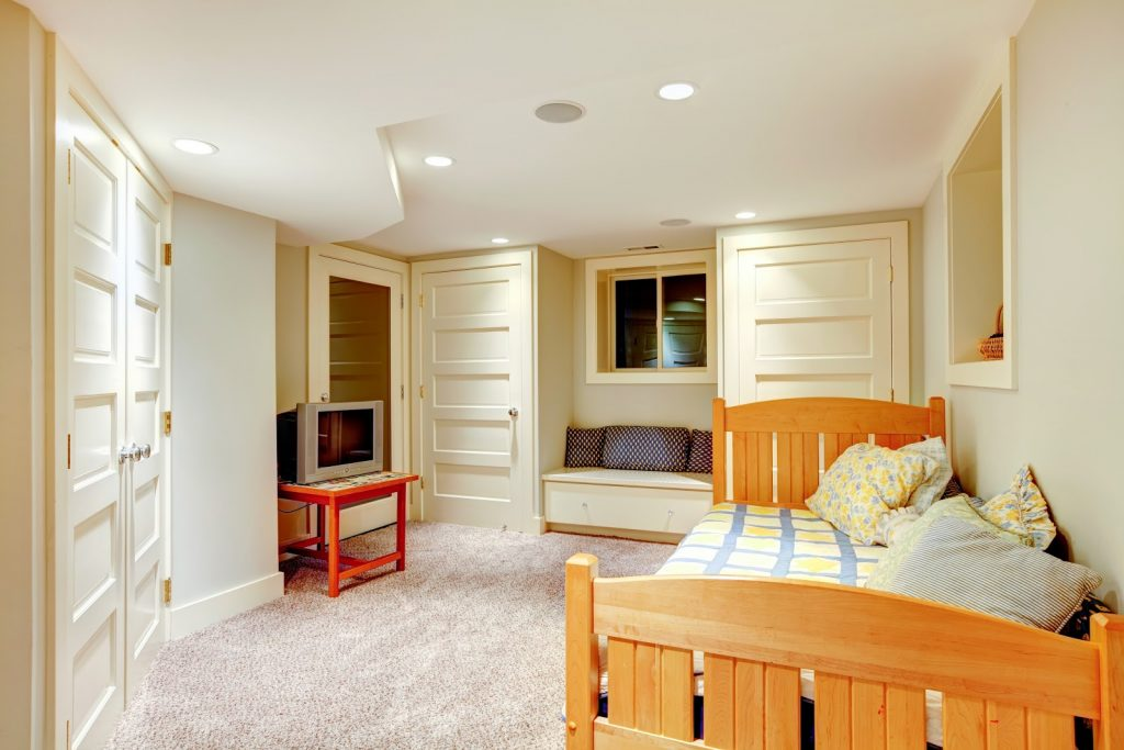 A basement bedroom with a sliding window