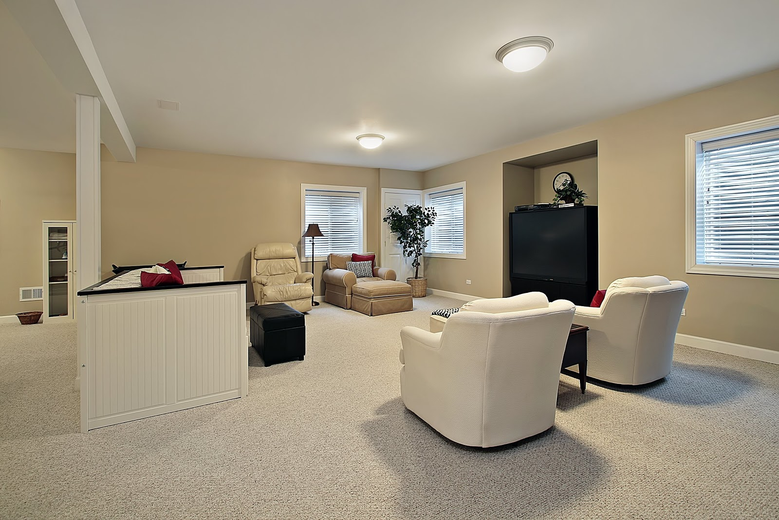 A fully finished basement used as a recreational area with basement windows