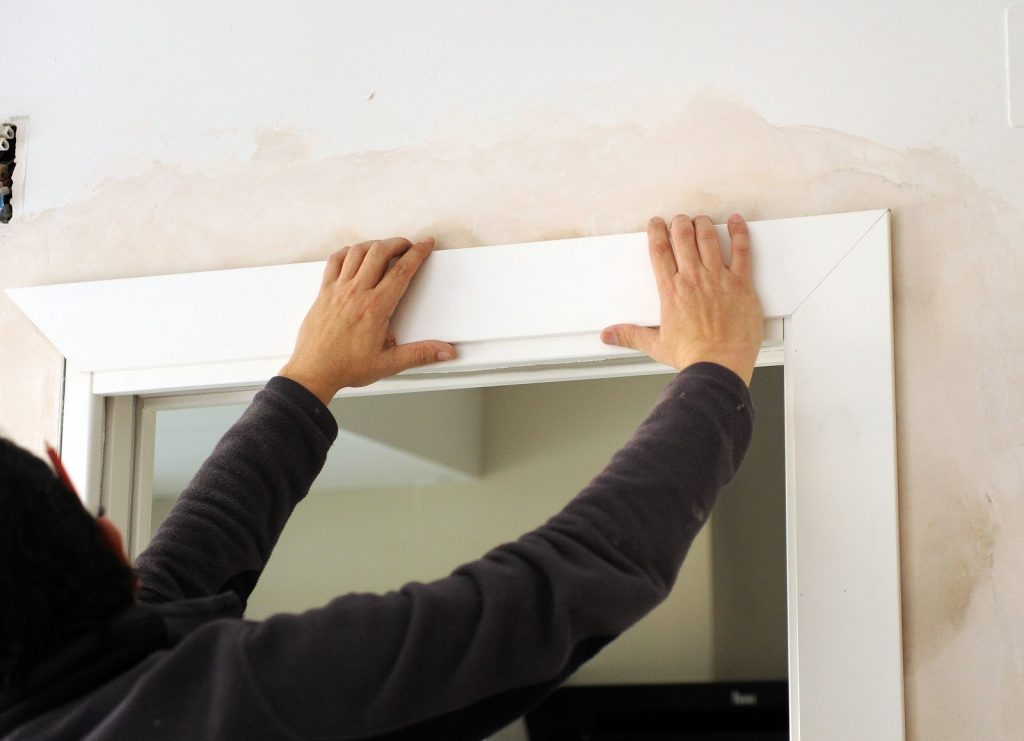 Close up of someone reinstalling door moulding or trims
