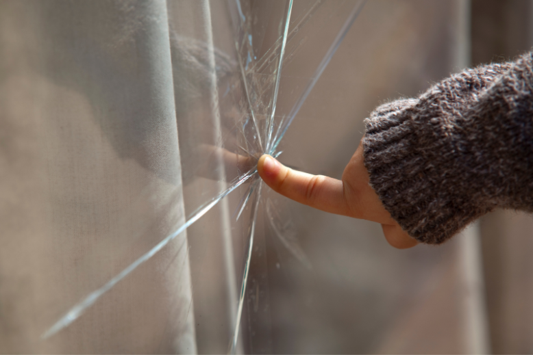 Close-up of a finger on cracked window glass