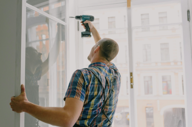 A man installing new insulated glass windows in a home