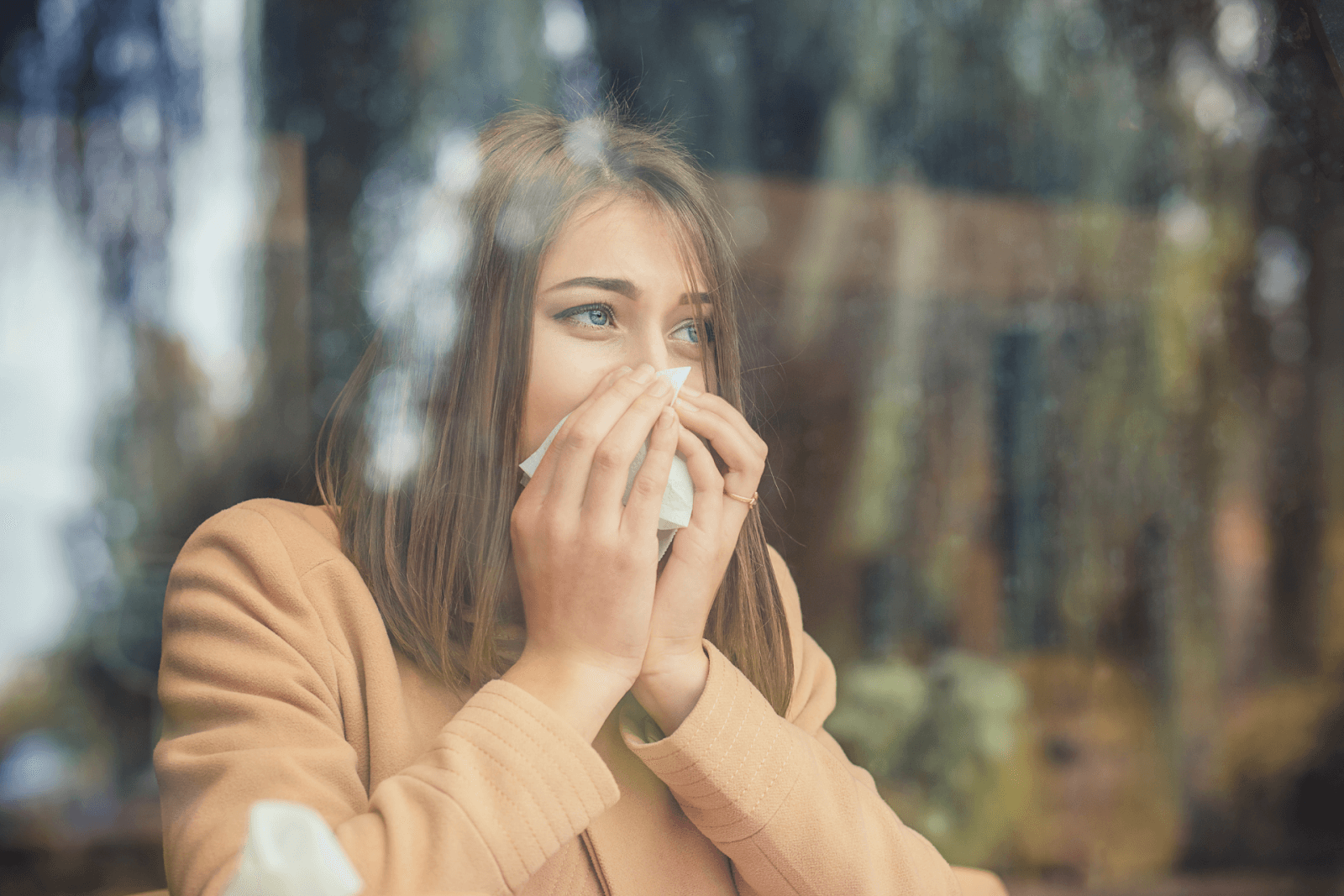 A woman standing in front of her window, sneezing from allergies