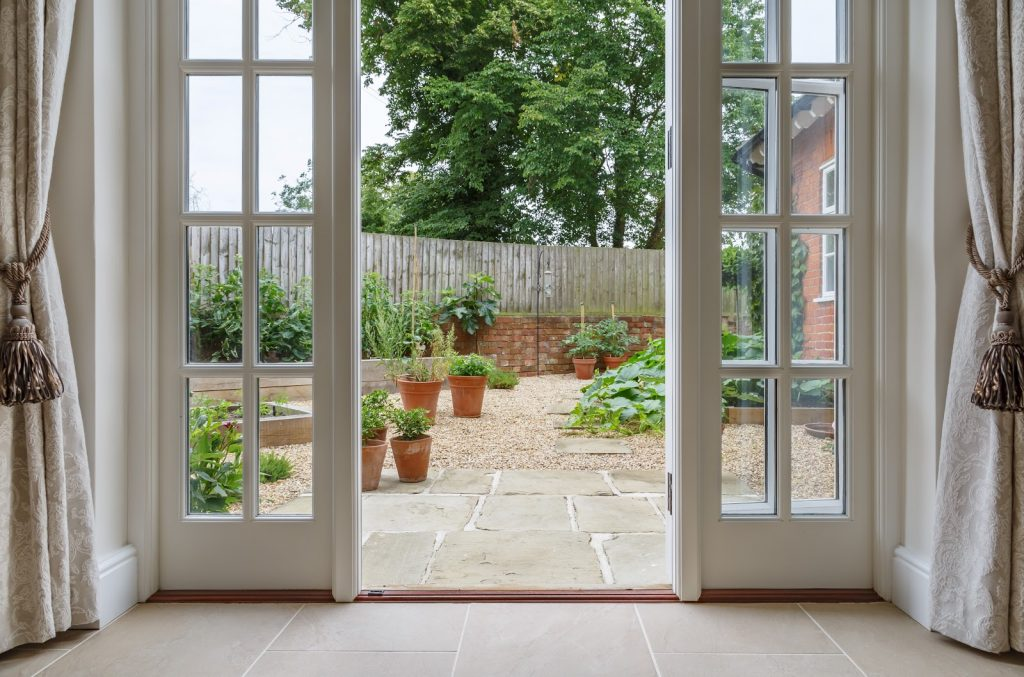 Garden Doors leading to a garden's paved path