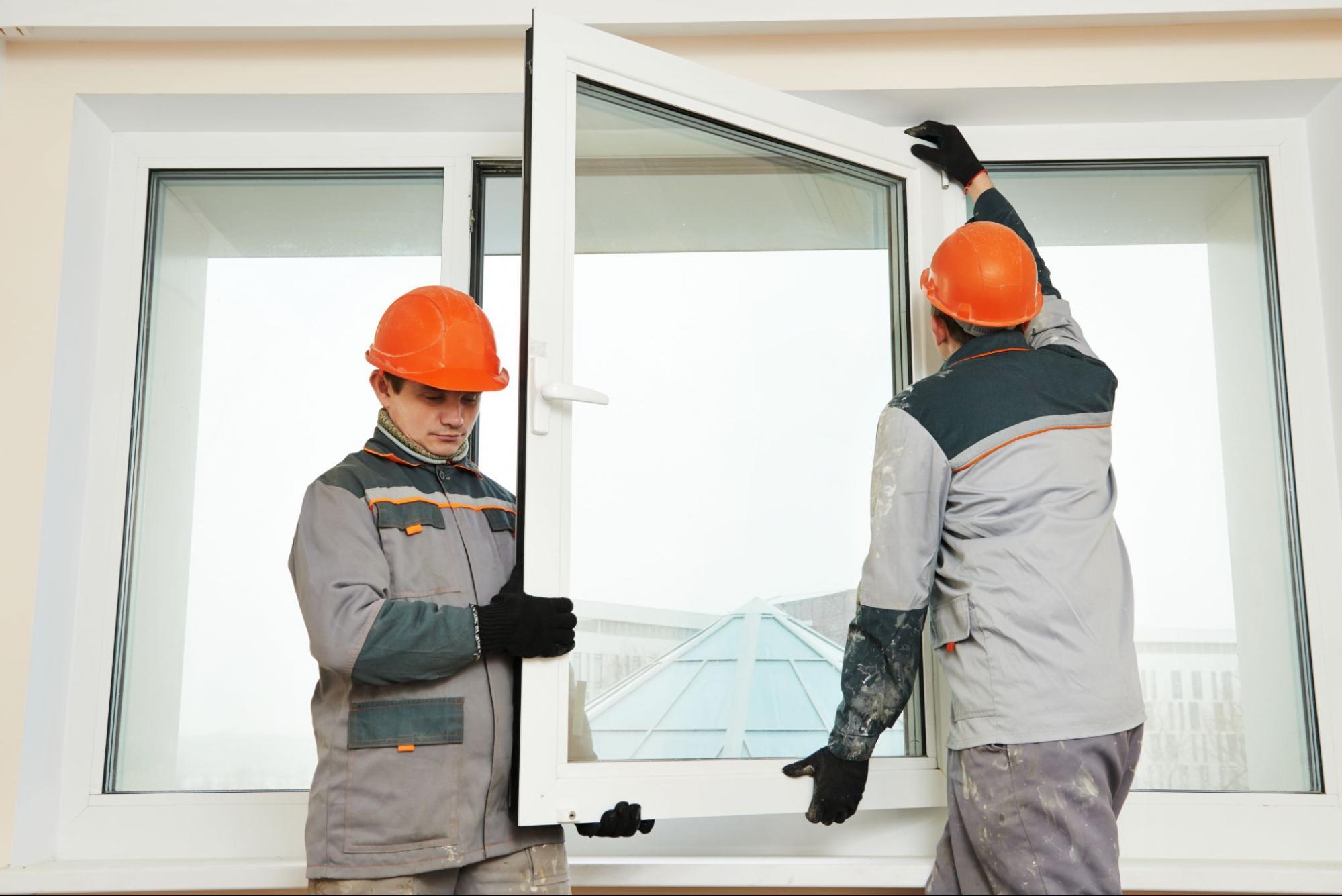 Two window installation specialists installing a brand new window