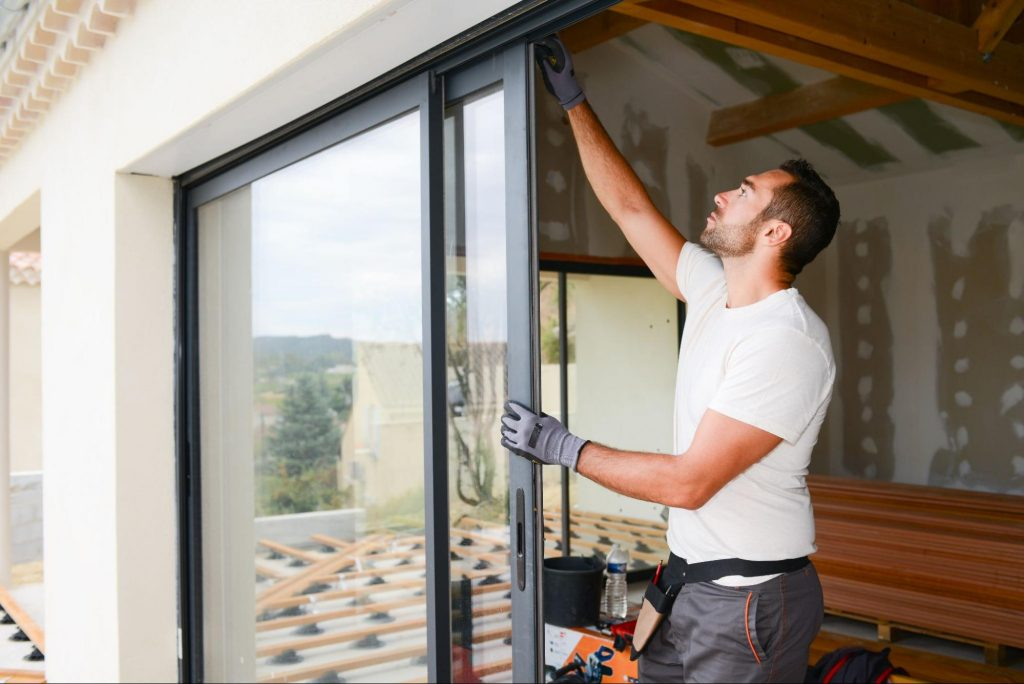 Serviceman installing a new sliding patio door