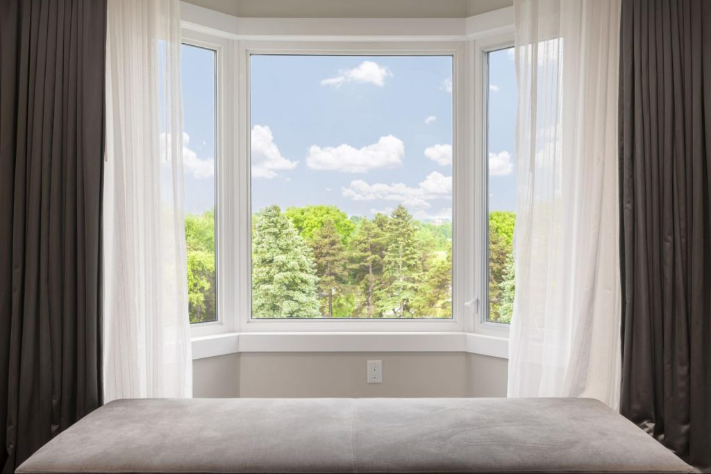 Vinyl bay windows looking out into a lush landscape