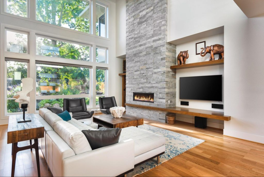 A living room with a window wall made of fixed windows extending up to the ceiling