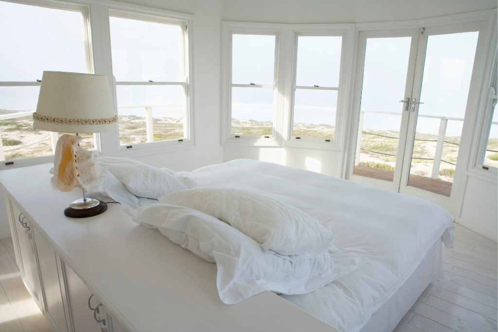 A white bedroom full of natural light with hung windows all around