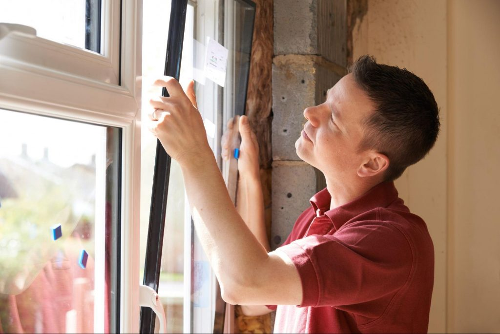 A photo of a man removing a window sash