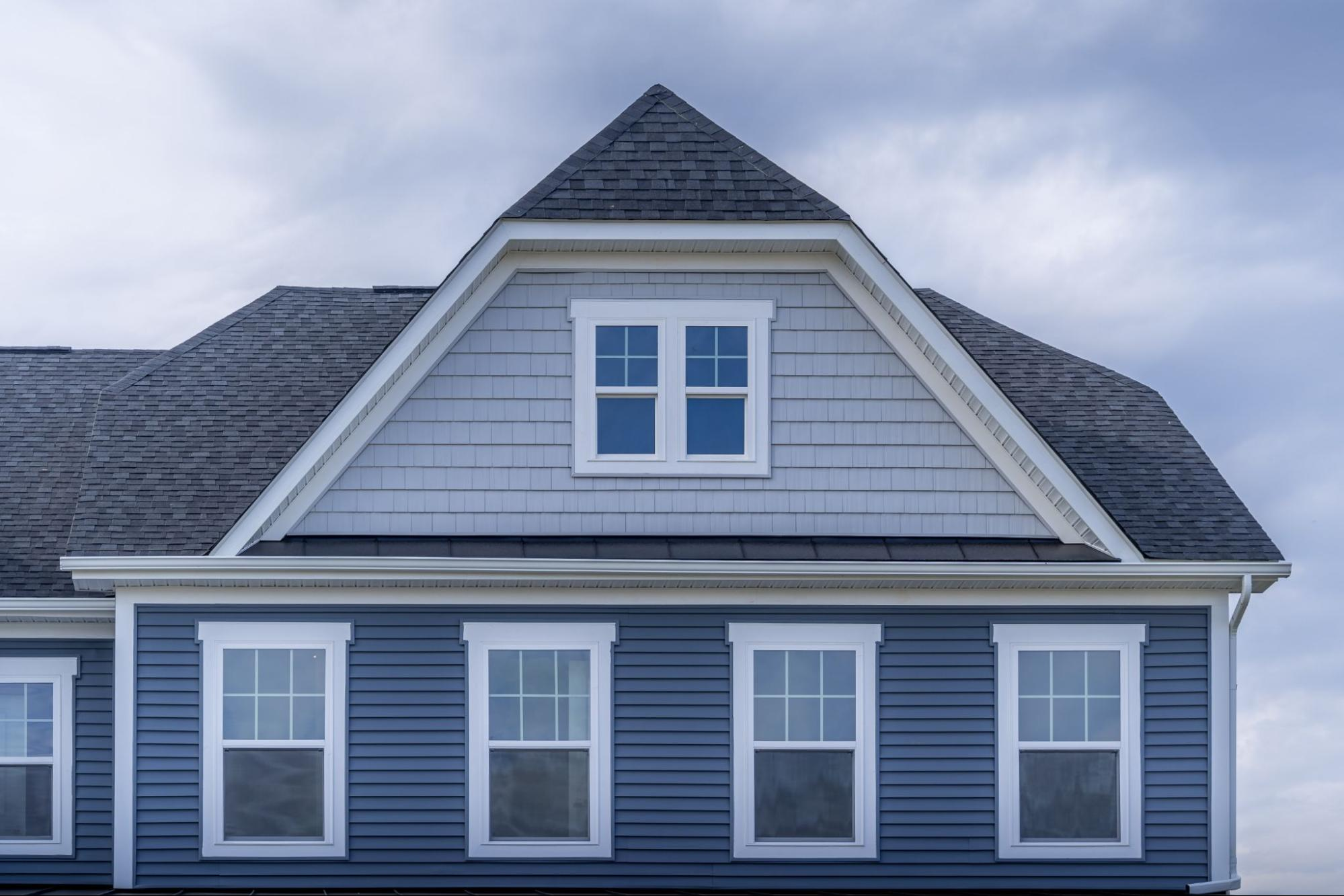 Cropped photo of a big blue house with hung windows