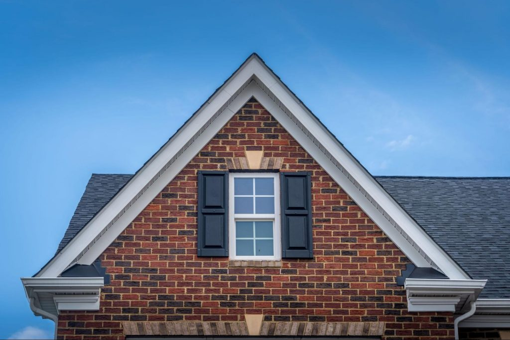 A hung window on a red-brick gable of a home