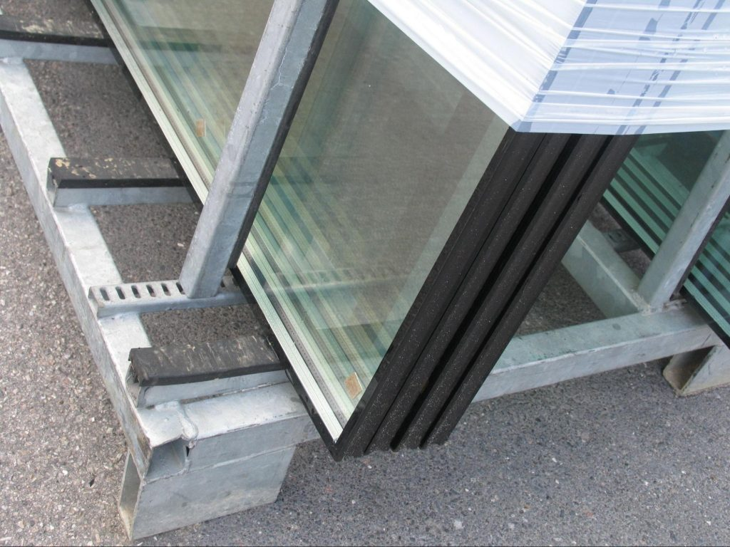 A set of sealed window units or insulated glass units on a metal rack