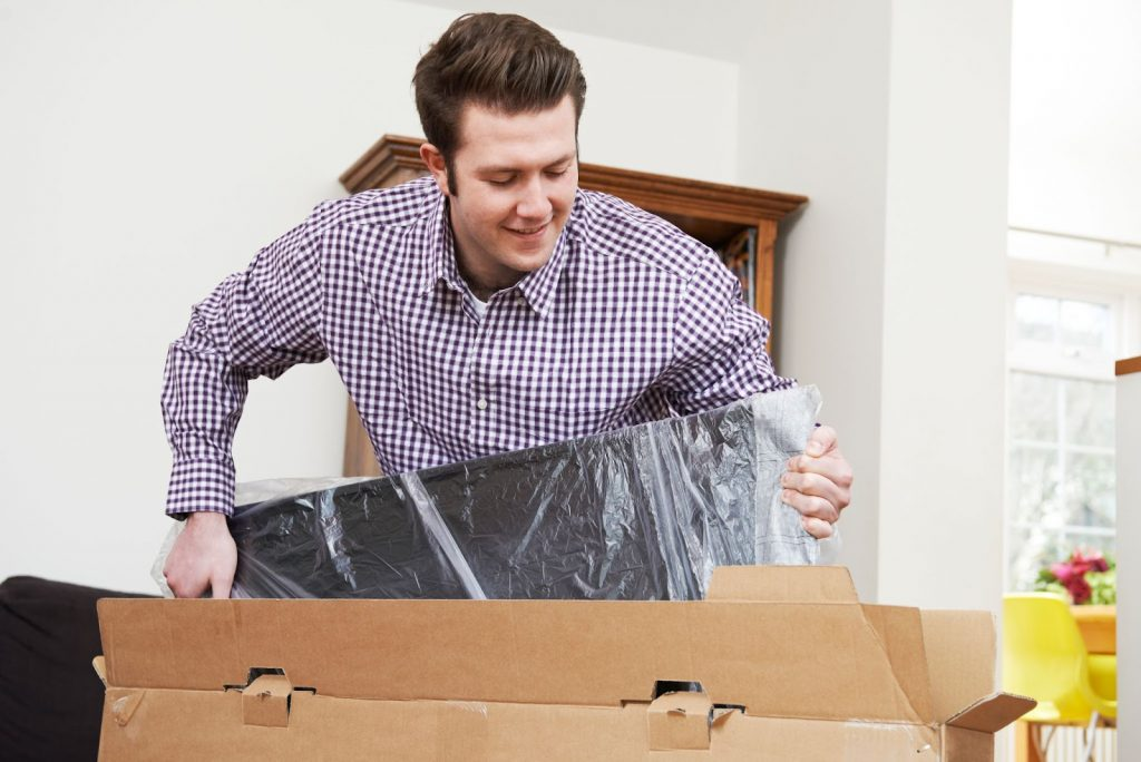 A man happily unpacking a new television set for his renovated home