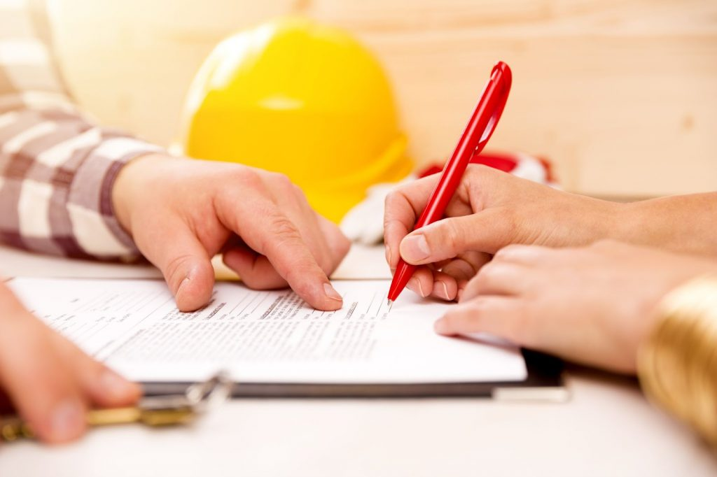 Closeup of a homeowner signing a contract with home improvement contractors