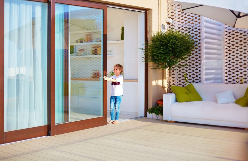 A young boy happily closing glass sliding doors in the patio