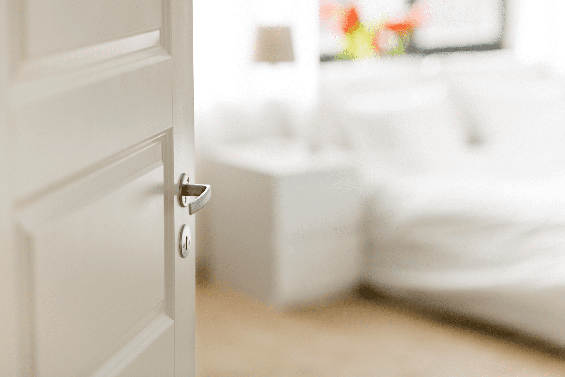 A white interior inswing door opening to a bedroom